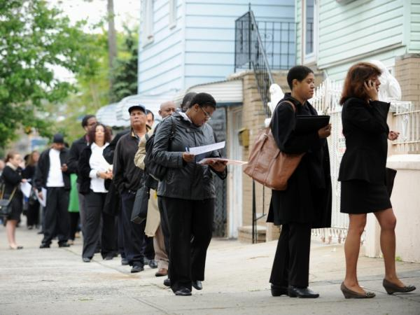 People seeking jobs wait in line to speak to employers at a career fair Thursday in the Queens borough of New York.