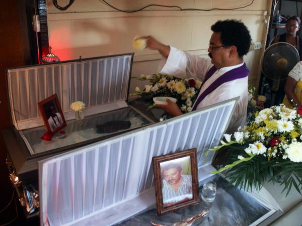A priest sprinkles holy water on the coffins of photojournalists Gabriel Huge (bottom) and Guillermo Luna during a public Mass in Veracruz last week. Killed by unknown assailants, the bodies were found dumped in plastic bags by a canal in Veracruz less than a week after the killing of Regina Martinez.
