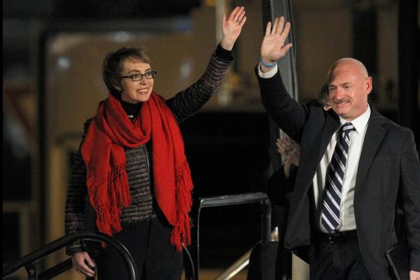 Arizona Rep. Gabrielle Giffords and her husband, Mark Kelly, wave at the start of a memorial in Tuscon, Ariz, on Jan. 8. The vigil marked the anniversary of the shooting rampage that left six dead and 13 injured, including Giffords.