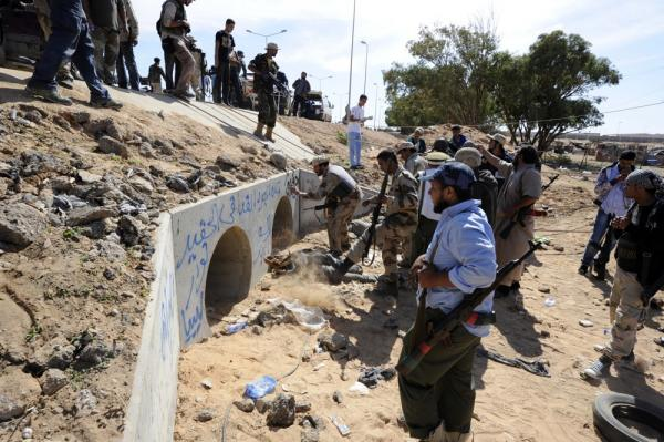 Libya NTC fighters gather outside large concrete pipes where Gadhafi was allegedly captured.