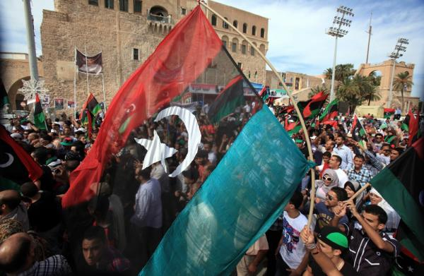 Libyans wave their new national flag as they celebrate in the streets of Tripoli. Gadhafi's capture marks the end of his 42-year rule.