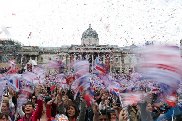 Well-wishers wave flags in Trafalgar Square to celebrate the wedding of Prince William and Kate Middleton on Friday.