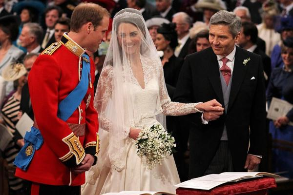 Prince William speaks to Kate Middleton as she holds the hand of her father, Michael, in Westminster Abbey in London on Friday.