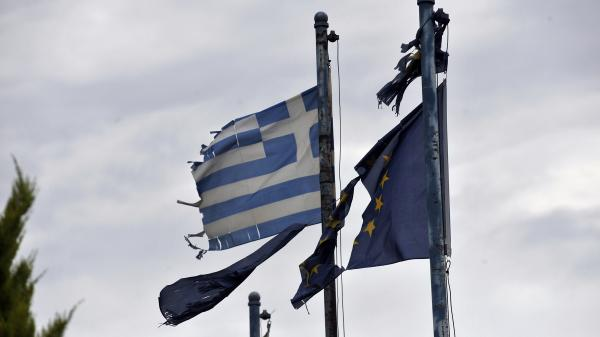 Torn Greek (left) and European Union flags fly at the entrance of an abandoned factory in the industrial zone of Komotini about 500 miles from Athens. Sunday's parliamentary election will go a long way toward determining whether Greece stays in the EU.