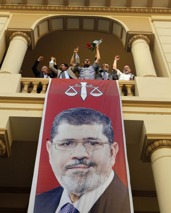 Egyptian campaign officials of the Muslim Brotherhood's candidate, Mohammed Morsi, celebrate over a giant poster of him at his campaign headquarters in Cairo, Egypt, Sunday.