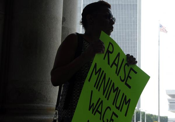 Wendy Brown of Schenectady, N.Y., holds a sign before an Occupy Albany rally pushing for a raise in New York's minimum wage on May 29, 2012.