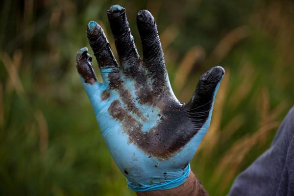 Bolenbaugh holds up a hand coated with oil sludge he has found in the Kalamazoo River two years after the spill, and two weeks after the state and EPA reopened the river to recreational use.