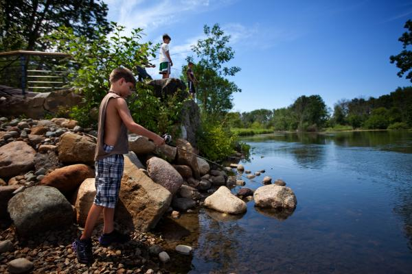 Children fish at a newly opened recreational area built by Enbridge on the Kalamazoo River. Posted signs warn that most of the fish is not safe to eat. These children were not aware of the oil spill and were not area residents.