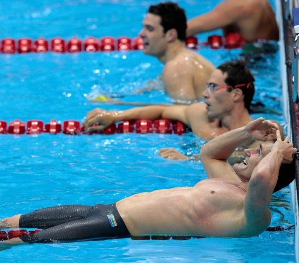 Cameron van der Burgh of South Africa celebrates his gold medal in the men's 100m breaststroke. He later admitted that he took extra dolphin kicks during his swim, a violation of the rules.