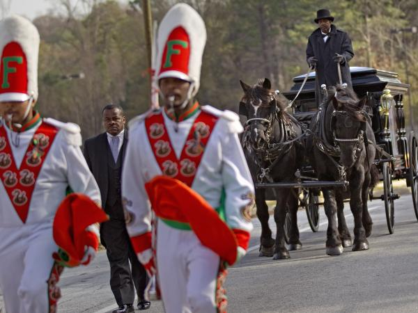 A horse-drawn carriage carrying the casket of Florida A&M University band member Robert Champion is led by his fellow band members following his funeral service in November.