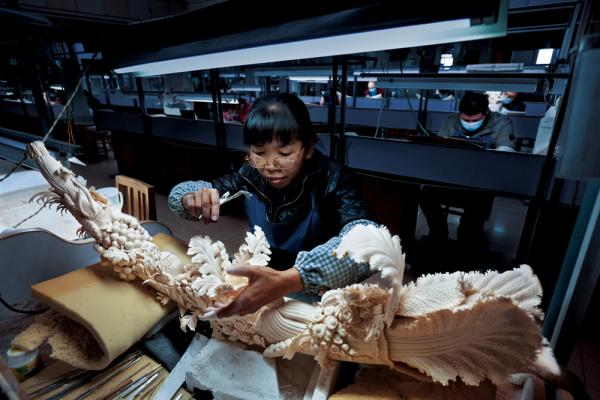 """A worker in China's largest ivory-carving factory finishes a piece symbolizing prosperity. China legally bought 73 tons of ivory from Africa in 2008; since then, poaching and smuggling have both soared."""