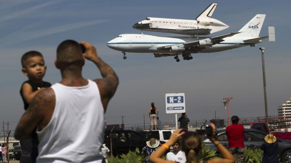Spectators Mario Vasquez, 40, of Redondo Beach and his son Mario Jr., 2, watch as space shuttle Endeavour, atop NASA's Shuttle Carrier Aircraft, prepares to land at Los Angeles International Airport Friday.
