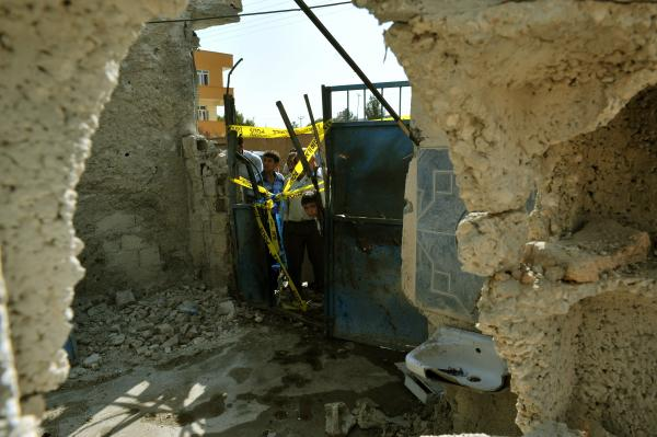 Local residents check on the damaged house where five Turkish civilians were killed on October 3 by a mortar bomb in the southern border town of Akcakale.