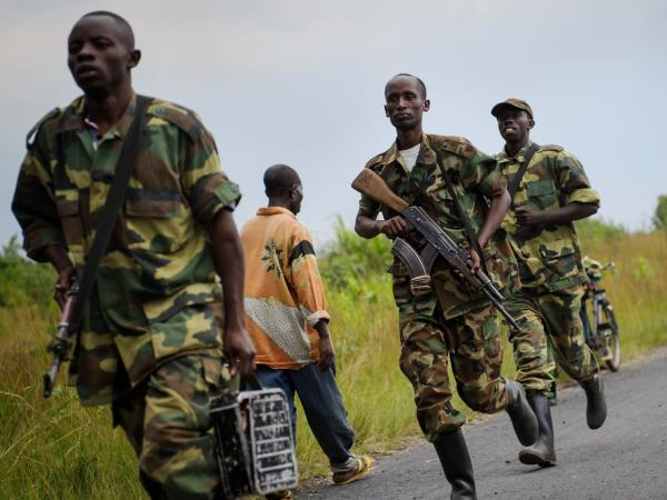 Congo rebels from the group known as M23 run toward the town of Sake in the eastern part of the country on Thursday. The rebels captured the town as part of their gains this week.