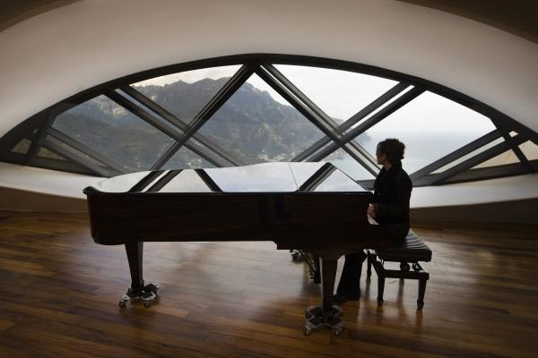 A pianist at Auditorium Oscar Niemeyer in Ravello on the day of its official inauguration in 2009, with Italy's Amalfi coast in the background.