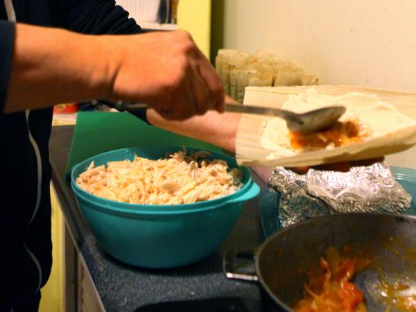 Crespo assembles tamales in his kitchen in the evening.
