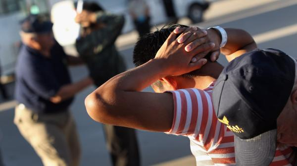 Employees with the U.S. Immigration and Customs Enforcement agency search Guatemalan immigrants before they are put aboard a deportation flight to Guatemala City on June 24, 2011, in Mesa, Ariz.