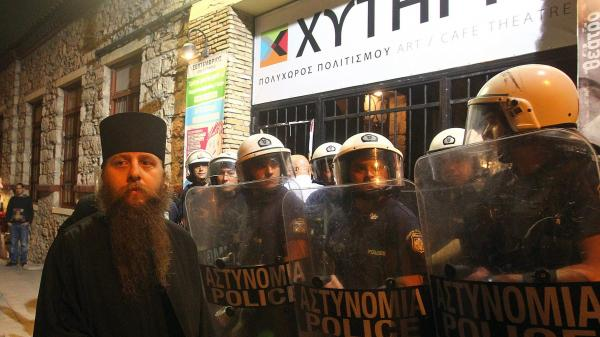 A Greek Orthodox priest is blocked by riot police as he takes part in a protest outside an Athens theater in October. The play, <em>Corpus Christi,</em> portrays Jesus and his apostles as gay men living in modern-day Texas. The director and the cast have been charged under Greece's blasphemy laws.