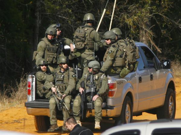 Law enforcement officials, including some from the FBI, near the scene of the hostage situation in Midland City, Ala., on Friday.