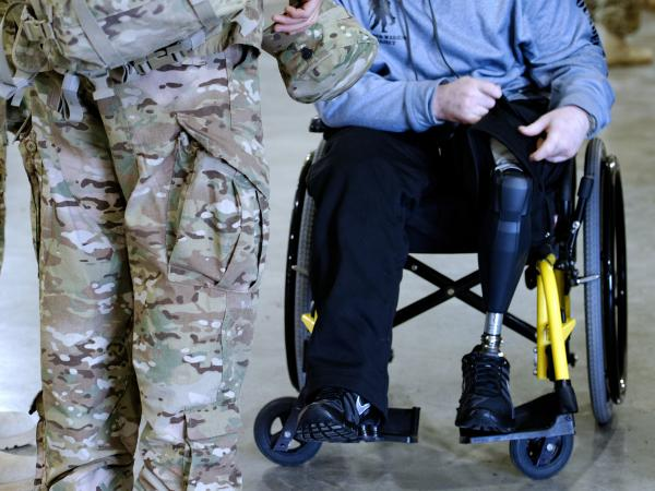 While his unit waits for buses to take them to a gym where family and friends will greet them, Jeffries sits in a wheelchair, one of his prosthetic legs visible.