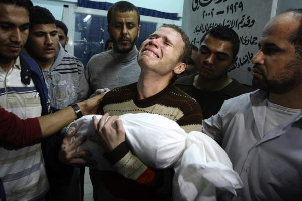 Jihad Masharawi weeps while he holds the body of his 11-month old son Ahmad.