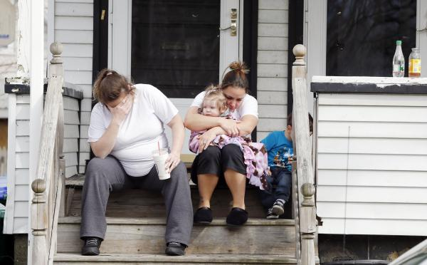 Neighbors sit outside the house of Krystle Campbell's parents in Medford, Mass., on Tuesday. Campbell was killed in the explosions at the finish line of the Boston Marathon on Monday.