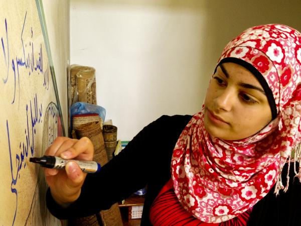 Yusra Hammed, 15, puts the finishing touches on a drawing on a wall inside her family's home in Silwad, a village in the West Bank. Hammed says, like many Palestinian girls, she does not throw rocks at Israeli soldiers; but she expresses her opposition through alternate channels, such as art.
