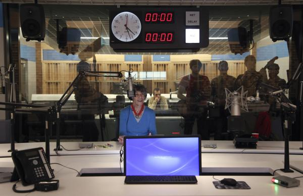 After trekking a few blocks down the road to NPR's new headquarters, the band surprises NPR 'Founding Mother' Susan Stamberg. Here, she's seated in Studio 31 as the crew films behind the glass.