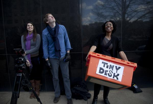 Off camera,<em> All Things Considered</em> Host Audie Cornish (far right) carries the Tiny Desk moving crate. Look for Cornish's and other NPR host and reporter cameos throughout the video.