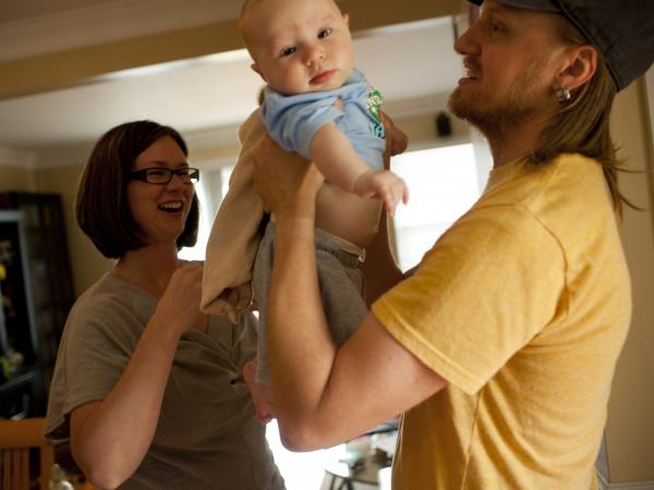 Dawn Heisey-Grove of Alexandria, Va., hands off son Zane to father Jonathan Heisey-Grove after a midday feeding. The couple were both working full time when Jonathan lost his job as a graphic designer two years ago. She's a public health analyst. He's now a stay-at-home dad.