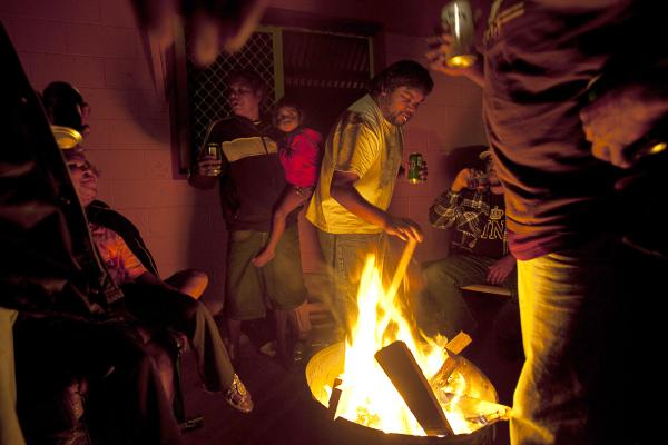 Friends and family gather around a fire in an Alice Springs town camp, Northern Territory. Town camps were established by squatters from remote communities seeking access to the public services available in towns. They have since become permanent communities with reputations for being dangerous at night.