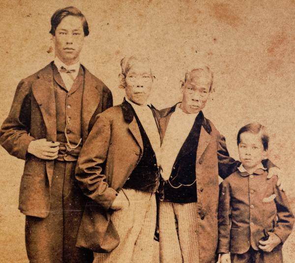 Eng Bunker stands with his 15-year-old son Patrick Henry (left), and Chang Bunker with his 8-year-old son Albert (right). This photo was taken circa 1865.