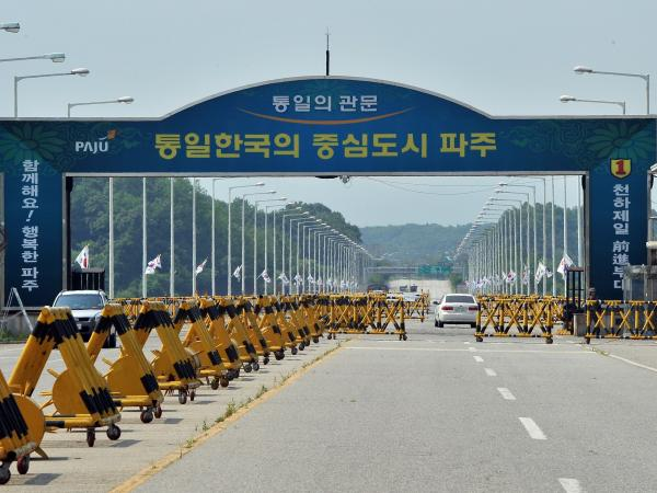 Cars drive past barricades on the road linking North Korea's Kaesong Industrial Complex at a military checkpoint in Paju, near the demilitarized zone dividing the two Koreas, on Thursday.