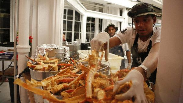 Chef Roblé Ali prepares crabs for an event with singer-songwriter John Legend.