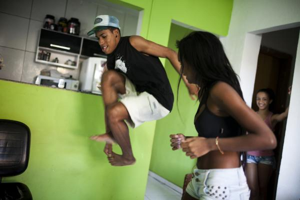 Costa practices <em>passinho</em> with Tais Castro, 14, in the Cidade de Deus neighborhood.  <em>Passinho</em> incorporates more feminine and free movements, which were repressed by Rio's <em>baile</em> funk dance style.