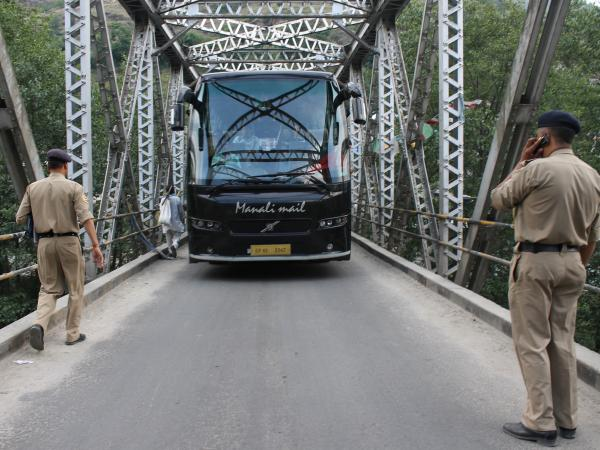 Indian police stop a tourist bus on Wednesday at a checkpoint put in place after the alleged rape of an American woman in the northern town of Manali.
