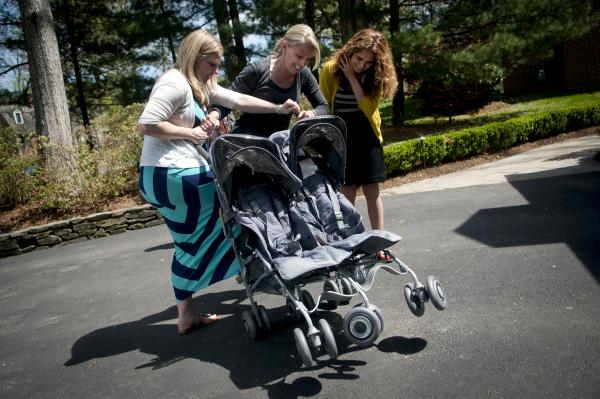 Costello's oldest sister, Megan Gipson (center), teaches Costello and Morales how to fold a twin-baby stroller in the family's driveway.
