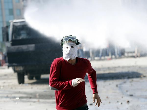 A protester runs as a crowd control vehicle fires a water cannon in Istanbul's Taksim Square on Tuesday.