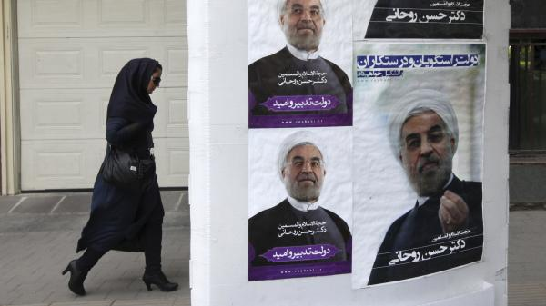 An Iranian woman walks past posters of presidential candidate Hasan Rowhani, a former top nuclear negotiator, next to his campaign headquarters, in Tehran, Iran, on June 1. Many Iranian women are concerned about the erosion of their opportunities.