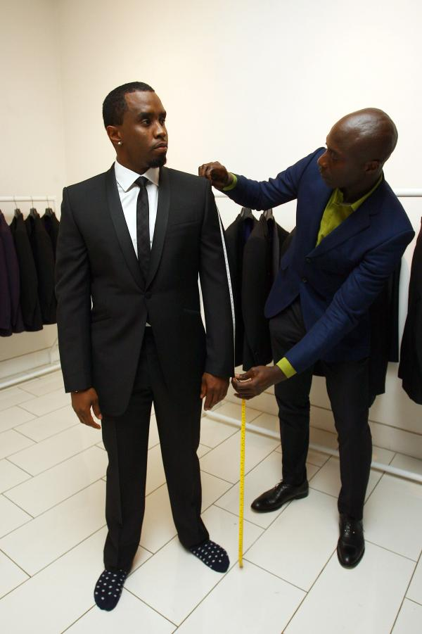 Boateng measures musician Sean Combs, aka P. Diddy, for a suit. His tailored suits cost as much as $40,000.