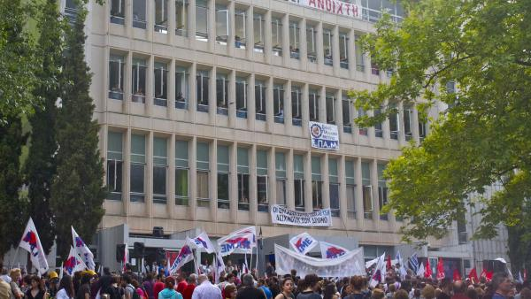 "Protesters bearing leftist union flags gather outside the main headquarters of  broadcaster ERT. Prime Minister Antonis Samaras shut down the network Tuesday, but workers are occupying the building. The top banner reads: ""ERT will remain open."""