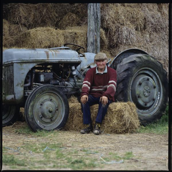 Robin Matthews sitting on hay bale with his tractor behind him, 1980s.