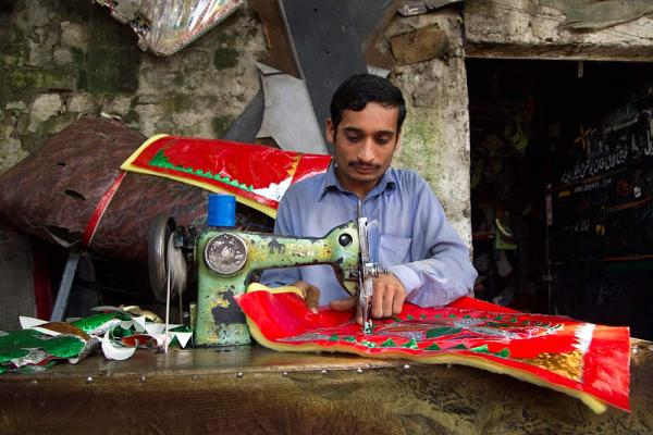 A young man stitches decorative seat covers and curtains in Rawalpindi, where he works for more than 12 hours a day.