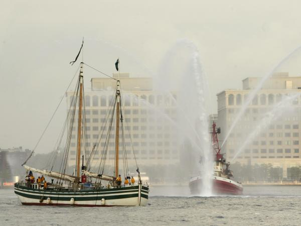 The Lois McClure (left) passes a fire boat as it arrives at New York's North Cove Marina in 2005. Canal schooners used wind power on open lakes, and lowered their masts and raised their centerboards to be towed through canals.