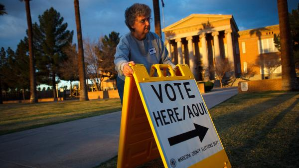 Election Day volunteer Vicki Groff places a sign to direct voters to a polling station at Kenilworth School in Phoenix in 2012.