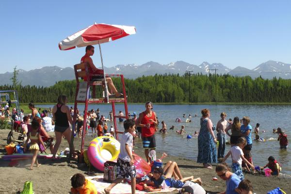 In this photo taken on Monday, people swim and sunbathe at Goose Lake in Anchorage, Alaska.