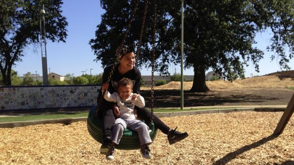 Micaela Torres and 2-year-old Jakai Johnson swing underneath a surveillance camera at Miwok Park in Elk Grove, Calif. The city's police department collects more than 100 video feeds from across the city.