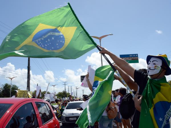 A protester waves a Brazilian flag over cars driving to the football stadium in Fortaleza, Northern Brazil, on June 19, 2013.
