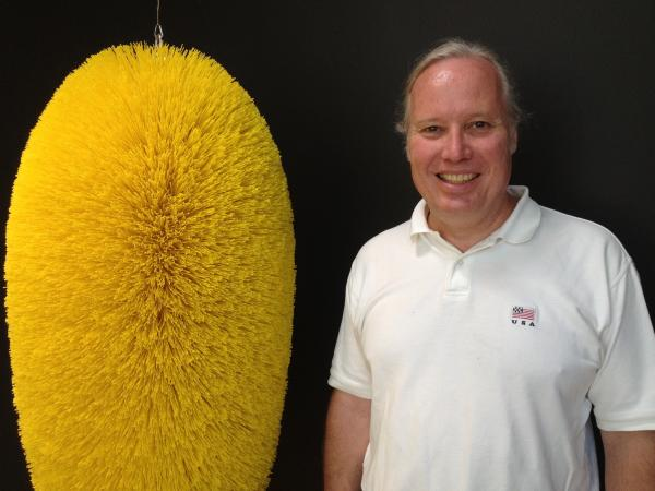 Fourth-generation owner of Braun Brush, Lance Cheney, stands next to a special-order brush his company made for the artist Richard Artschwager.