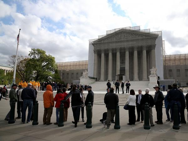 People line up to enter the Supreme Court building on April 22, when the court heard arguments in the <em>Agency for International Development v. Alliance for Open Society International</em> case.